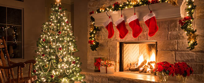 Decorated Christmas tree next to a fireplace and decorated mantel