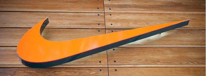 Orange Nike swoosh on wood background