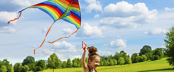 Girl flying a kite in the park)